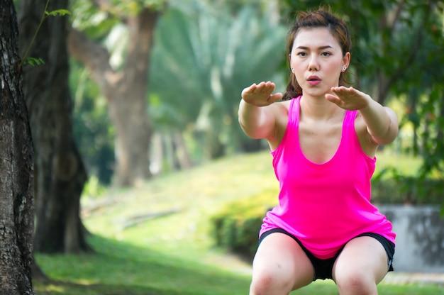 Femme de sport asiatique se réchauffer pour exercer en squat de poids corporel dans le parc