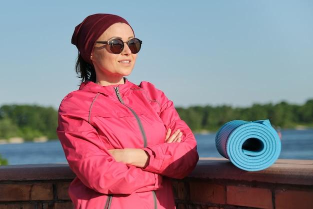 Femme de sport confiant d'âge moyen avec tapis de yoga