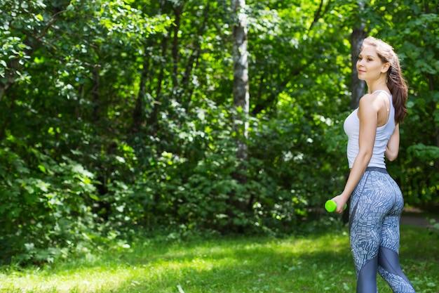 Femme de sport, faire des exercices avec haltères en plein air