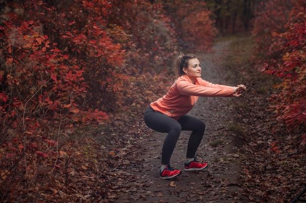 Femme de sport fatigué en vêtements de sport dans la forêt d'automne