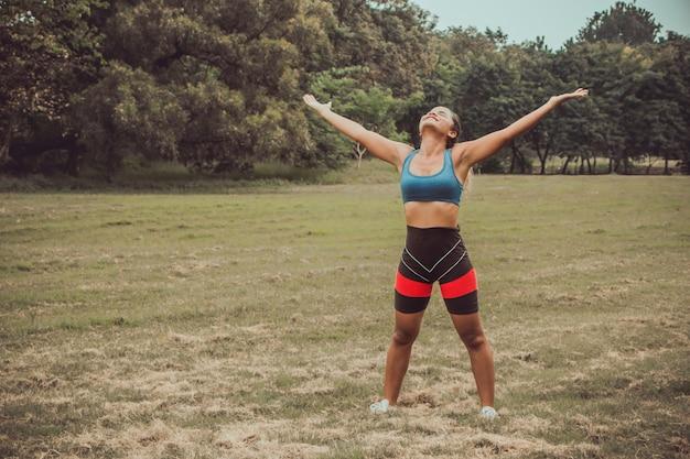 Femme sport féminin levant les mains dans le succès, la liberté, la confiance, le concept de motivation.