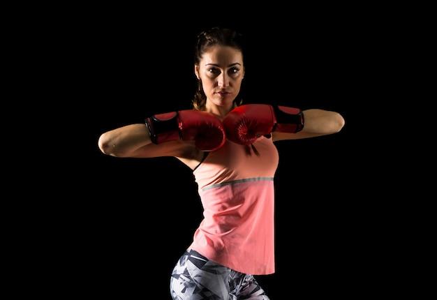 Femme de sport sur fond sombre avec des gants de boxe