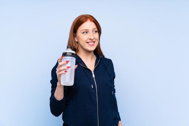 Femme sport jeune rousse sur mur bleu isolé avec bouteille d'eau de sport