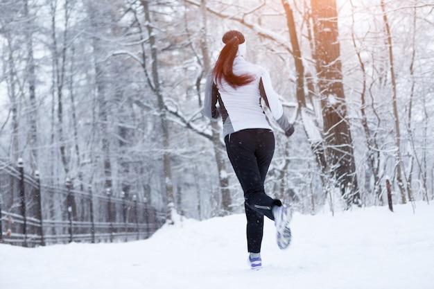 Femme sport jogging le matin du parc d'hiver