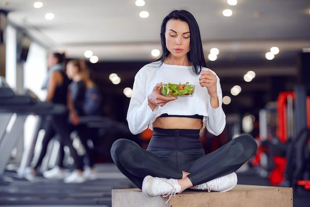 Femme de sport mangeant de la salade