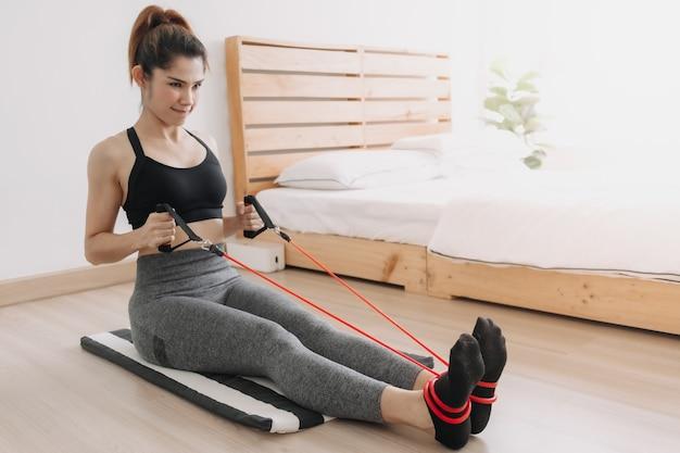 Une femme en sport porte une bande de résistance assise en pronation dans sa chambre