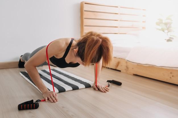 Une femme en sport porte une bande de résistance dans sa chambre