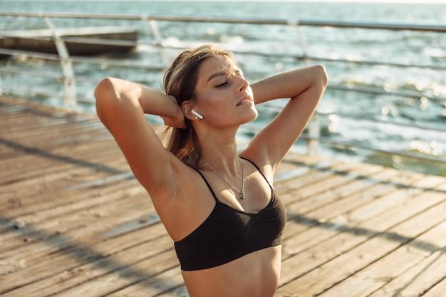 Femme de sport de remise en forme relaxante sur la plage, écoutant de la musique dans un casque au lever du soleil