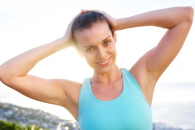 Femme de sport souriant avec les mains derrière la tête
