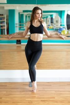 Femme de sport en vêtements de sport de mode qui s'étend du corps.