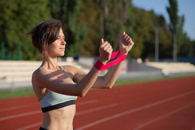 Femme sportive adulte faisant de l'exercice avec les mains avec une bande élastique en plein air le matin. espace libre