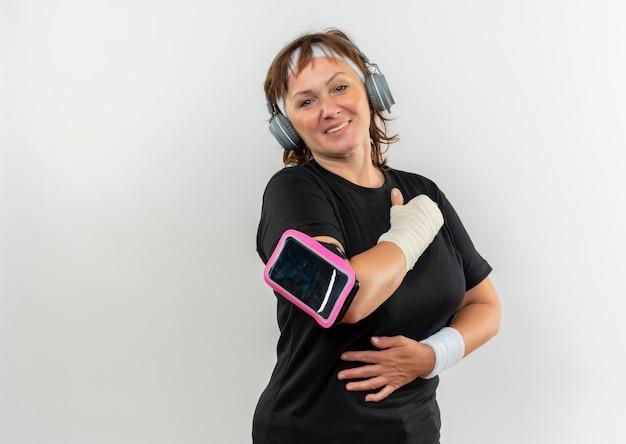 Femme sportive d'âge moyen en t-shirt noir avec bandeau et brassard de smartphone tenant la main sur sa poitrine se sentant reconnaissant debout sur un mur blanc