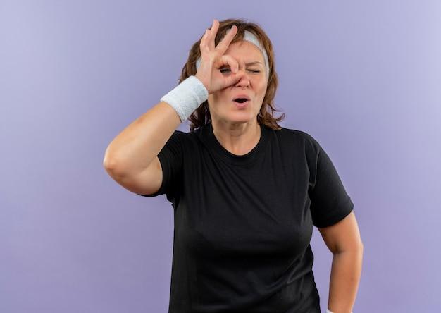 Femme sportive d'âge moyen en t-shirt noir avec bandeau faisant signe ok à travers ce signe surpris debout sur mur bleu
