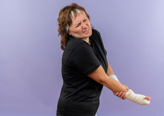 Femme sportive d'âge moyen en t-shirt noir avec bandeau à la recherche de mal tenant son poignet bandé ayant de la douleur debout sur le mur bleu