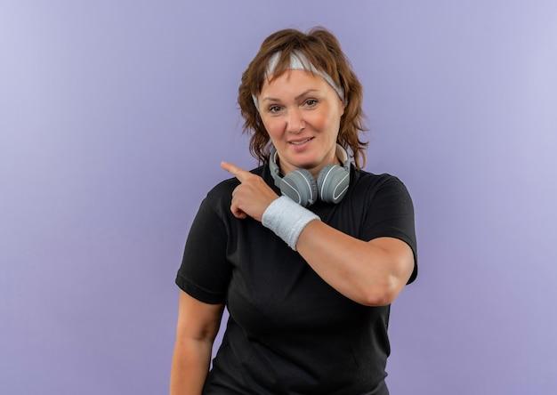 Femme sportive d'âge moyen en t-shirt noir avec bandeau avec sourire sur le visage pointant vers le côté debout sur le mur bleu