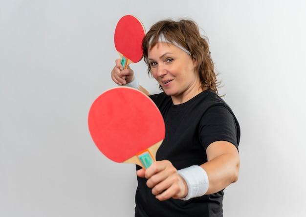 Femme sportive d'âge moyen en t-shirt noir avec bandeau tenant deux raquettes de tennis de table avec sourire sur le visage debout sur un mur blanc