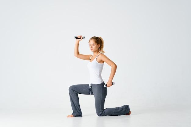 Femme sportive agenouillée exercice de motivation d'entraînement avec des haltères