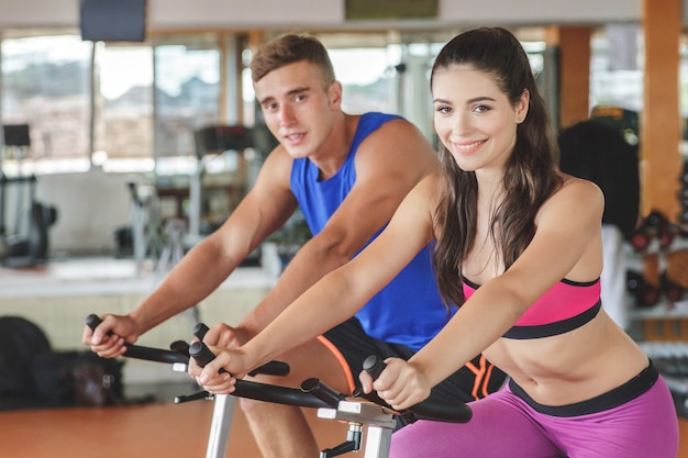Femme sportive à l'aide d'un vélo d'exercice avec son partenaire de remise en forme