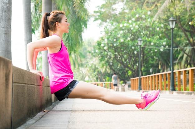 Femme sportive asiatique qui s'étend dans le parc après la course