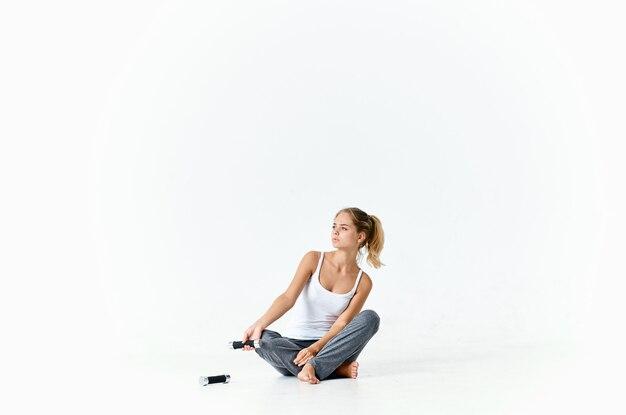 Femme sportive assise sur le sol avec des muscles d'entraînement d'haltères