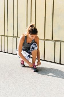 Femme sportive attachant des chaussures en milieu urbain