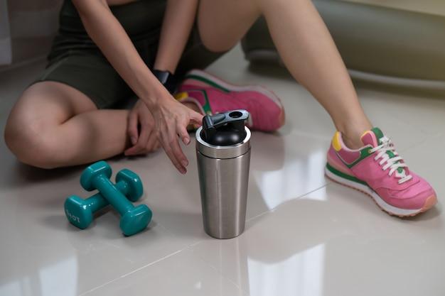 Femme sportive au repos après l'entraînement avec bouteille de boisson protéinée sur marbre