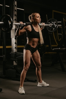 Une femme sportive aux cheveux blonds commence à s'accroupir avec une barre près du support de squat dans une salle de sport. une fille fait une séance d'entraînement des jambes.