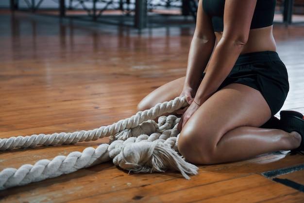 Femme sportive blonde fait de l'exercice avec des cordes dans la salle de gym.