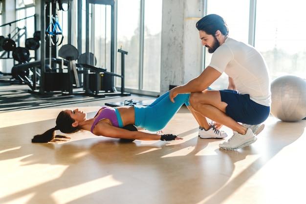 Femme sportive caucasienne mince avec queue de cheval, faire des exercices tandis que l'entraîneur personnel accroupi à côté d'elle et l'aidant.