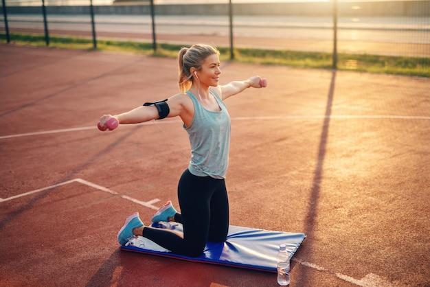 Femme sportive caucasienne souriante travaillant avec des haltères sur le court le matin.