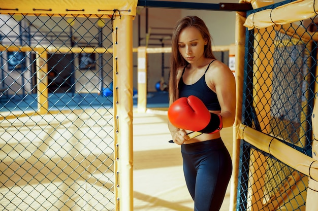 Une femme sportive combattante mma en gants de boxe pose dans une cage en salle de sport