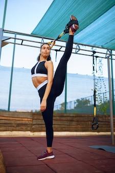 Femme sportive avec un corps parfait faisant des exercices d'étirement avec des cordes sur un terrain de sport à l'extérieur