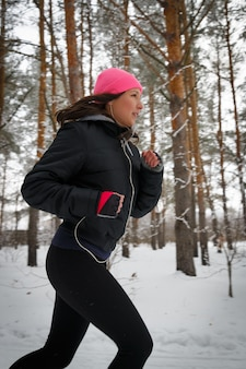 Femme sportive en cours d'exécution. coureuse de jogging dans la forêt d'hiver froid portant des vêtements de course sportifs chauds et des gants d'écouteurs. beau modèle de fitness féminin en forme.