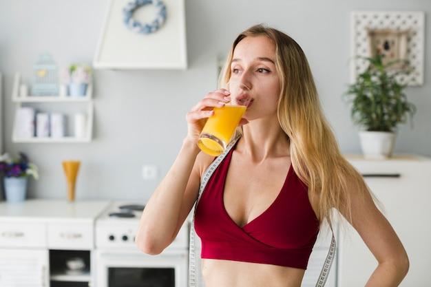 Femme sportive dans la cuisine avec du jus de fruits