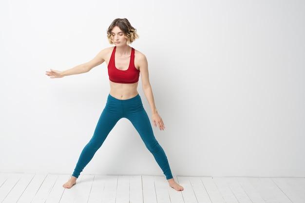 Femme sportive dans une pièce lumineuse faisant du yoga posant contre le mur