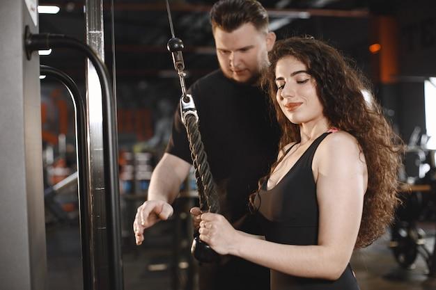 Femme sportive dans la salle de gym. un homme effectue des exercices. mec en t-shirt.