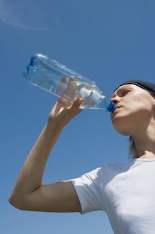Une femme sportive a de l'eau d'une bouteille sur un ciel bleu