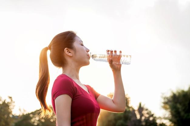 Femme sportive eau potable sur la lumière du soleil.
