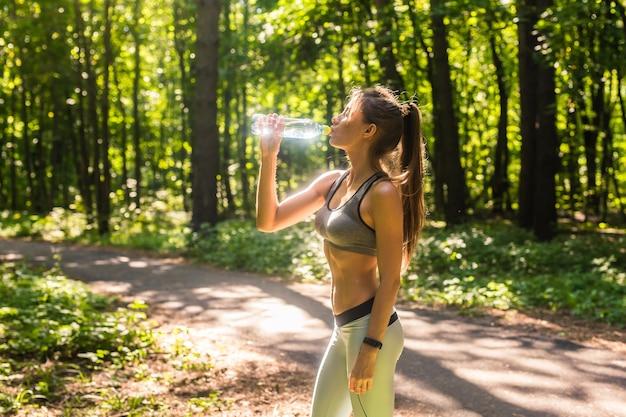 Femme sportive eau potable en plein air par une journée ensoleillée.