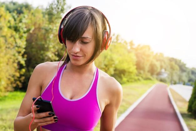 Femme sportive écoutant de la musique pendant l'entraînement dans un parc