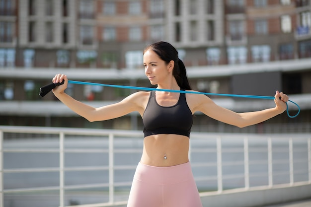 Femme sportive élancée faisant de l'exercice avec les mains avec une corde à sauter près du stade