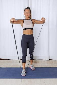 Femme sportive avec équipement de résistance travaillant à la maison