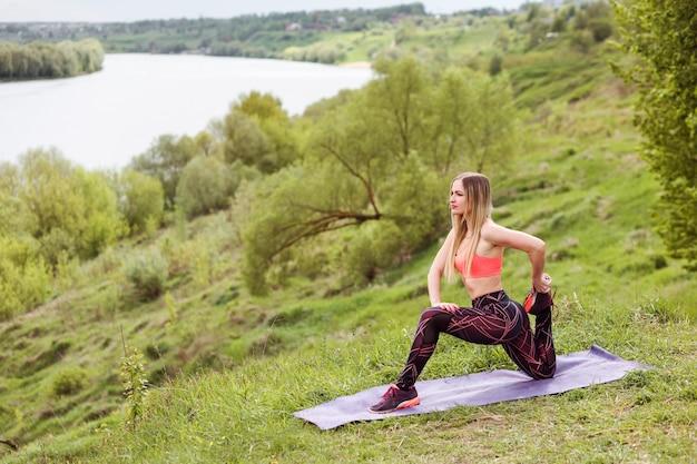 La femme sportive étire sa jambe, s'exerçant sur la rive de la rivière en été.