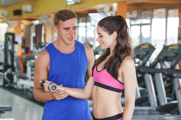 Femme sportive exerçant avec son instructeur au gymnase