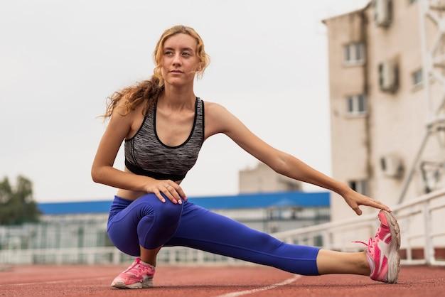 Femme sportive à faible angle, échauffement