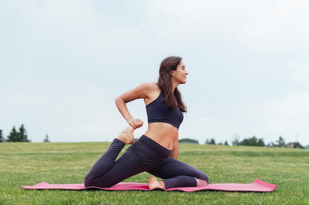 Femme sportive, faire du yoga en plein air