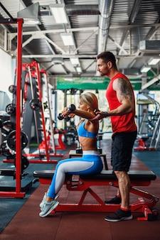 Femme sportive, faire des exercices de musculation avec l'aide de son entraîneur personnel au gymnase