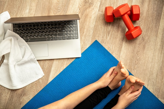 Femme sportive faisant du yoga fitness s'étirant à la maison via un ordinateur portable. jeune femme perdant du poids par une séance d'entraînement en ligne à l'aide d'haltères sur la vue de dessus du sol de la maison. santé et bien-être du corps.