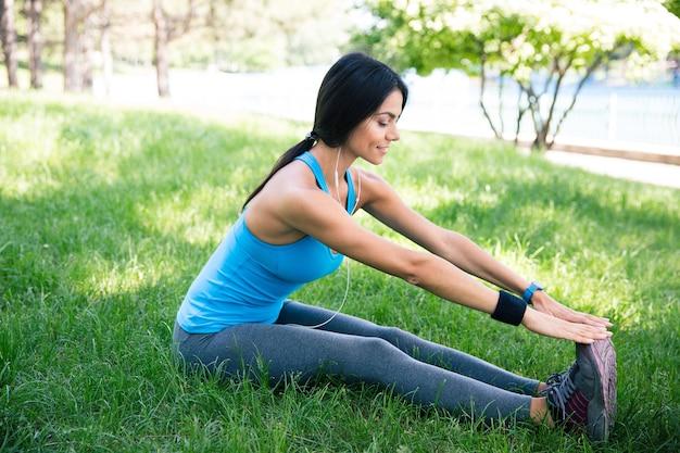 Femme sportive faisant des exercices d'étirement dans le parc