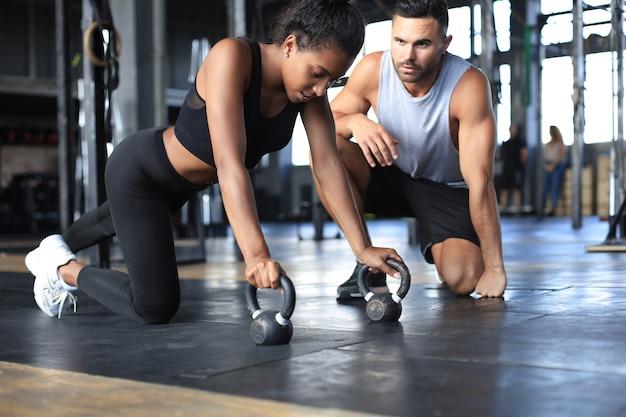 Femme sportive faisant des pompes dans une salle de sport, son petit ami la regarde.